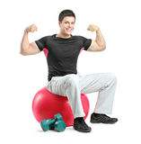 A young bodybuilder sitting on a pilates ball Royalty Free Stock Images