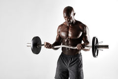 Young bodybuilder training over grey background. Studio shot of young bodybuilder training over grey background. Muscular african male model lifting barbell Stock Image
