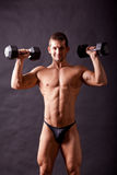 Young bodybuilder traininig. Over balck background Stock Photos