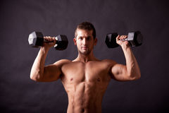 Young bodybuilder traininig. Over balck background Stock Image