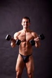 Young bodybuilder traininig. Over balck background Royalty Free Stock Images