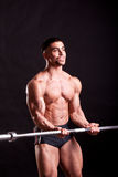 Young bodybuilder traininig. Over balck background Royalty Free Stock Photo