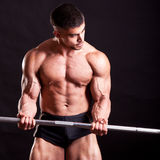 Young bodybuilder traininig. Over balck background Stock Photography