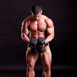 Young bodybuilder traininig. Over balck background Royalty Free Stock Photography