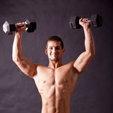 Young bodybuilder traininig. Over balck background Royalty Free Stock Image