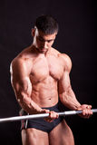Young bodybuilder traininig. Over balck background Stock Images