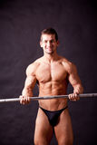 Young bodybuilder traininig. Over balck background Stock Photo