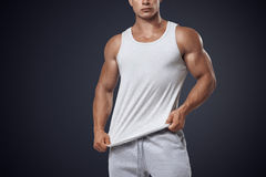 Young bodybuilder wearing white sleeveless t-shirt Royalty Free Stock Photography