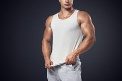 Young bodybuilder wearing white sleeveless t-shirt. Close up photo of attractive bodybuilder wearing blank white sleeveless t-shirt, vest Royalty Free Stock Images