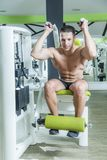 Abs exercise on a machine. Young bodybuilder working out in gym, doing ab exercise crunches using a machine Stock Photography