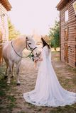 Young boho style bride is stroking white horse royalty free stock images