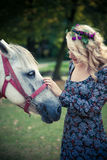Young boho style woman pat horse in park summer day Royalty Free Stock Images