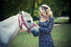 Young boho style woman pat horse in park summer day Royalty Free Stock Image