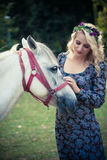 Young boho style woman pat horse in park summer day Stock Photos