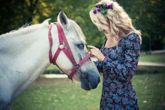 Young boho style woman pat horse in park summer day Stock Images