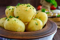 Young boiled potatoes with butter and dill in a clay bowl on a wooden background. Royalty Free Stock Photography