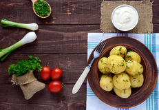 Young boiled potatoes with butter and dill in a clay bowl on a wooden background. Royalty Free Stock Image