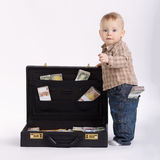 Young bookkeeper with suitcase of money. Little young bookkeeper with suitcase of money royalty free stock image