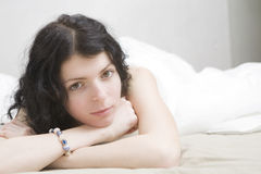 Young bored brunette woman lying down on bed Stock Image