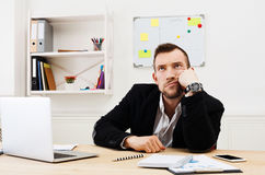 Young bored businessman with laptop in modern white office Royalty Free Stock Photo