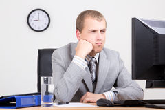Young bored businessman sitting in office Royalty Free Stock Images