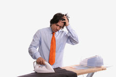 Young bored bussinessman doing the ironing Stock Image