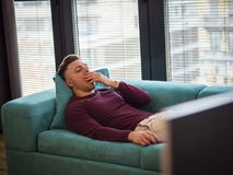 Young bored man laying on sofa watching TV. Young bored man lying on sofa watching television changing the channel with the remote control royalty free stock images