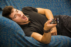 Young bored man sitting on sofa watching Stock Photography