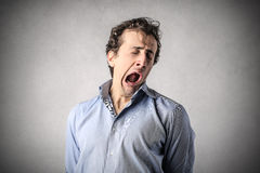 Young bored man. Young man yawning with a very bored expression Royalty Free Stock Photos