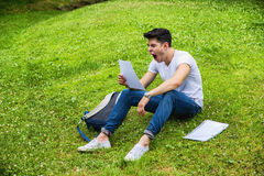 Young Bored, Tired Male Student Studying in City. Young Bored, Tired Male Student Studying his Lessons while Yawning, Sitting on Grass in City Park, Smiling at Stock Images