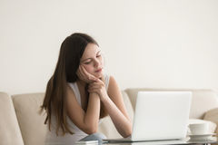 Young bored woman feeling drowsy at home sitting with laptop. Young bored woman feels drowsy sitting on couch at home near laptop, lazy jobless student spends Royalty Free Stock Image