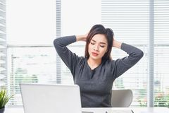 Young bored woman feeling drowsy at office sitting with laptop computer.  royalty free stock image