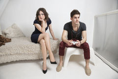 Young bored woman sitting on sofa with man playing video game Stock Photography