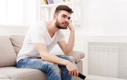 Young boring man watching television at home. Young man watching television, using remote control to switch channels. Guy bored with what he sees on TV screen Royalty Free Stock Images