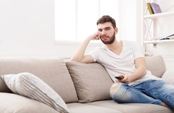 Young boring man watching television at home. Young man watching television, using remote control to switch channels. Guy bored with what he sees on TV screen Stock Images