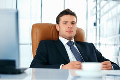Young Boss. Young business executive sitting relaxed in chair looing at you Royalty Free Stock Photos