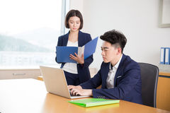 Young boss and assistant at work. Chinese young handsome young men is boss, and assistant at work talk royalty free stock image