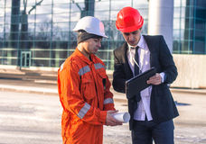 Young boss Scold Employee in conversation discussing a construct. Ion project on tablet. They wear  safety helmets. Business modern background Stock Photography