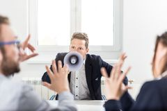 Young boss shouting at employees through megaphone in conference room royalty free stock photography
