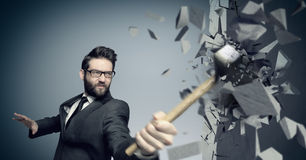 Young boss smashing a wall with a hammer Stock Image