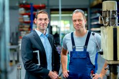 Young boss and worker in the factory. In the factory- young boss and worker in the factory stock photos