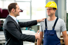 Young boss and worker in factory. Young boss is lauding worker in factory Stock Image