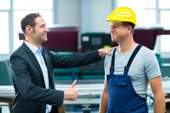 Young boss and worker in factory. Young boss is lauding worker in factory Stock Photos