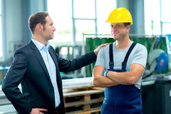 Young boss and worker in factory Stock Photography