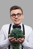 Young botanist. Portrait of cheerful young man in bow tie and suspenders holding a plant in his hands and smiling while standing against grey background Royalty Free Stock Photography