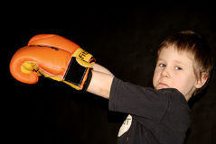 Young boxer. A young boy wearing boxing gloves, serious competitive expression on his face, black background royalty free stock photos
