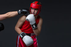 Young boxer is being punched. Teenage boxer in red form and helmet is being punched into face. Studio shot on black background. Copy space Royalty Free Stock Photos