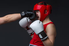 Young boxer is being punched. Teenage boxer in red form and helmet is being punched into face. Studio shot on black background. Copy space Royalty Free Stock Photo