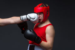 Young boxer is being punched. Teenage boxer in red form and helmet is being punched into face. Studio shot on black background. Copy space Stock Photography