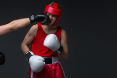 Young boxer is being punched. Teenage boxer in red form and helmet getting punched into face. Studio shot on black background. Copy space Stock Images
